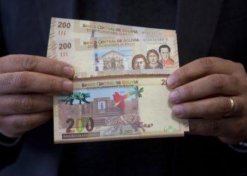 Un empleado del Banco Central de Bolivia maneja los nuevos billetes de 200 bolivianos durante una ceremonia en el palacio de gobierno de La Paz, el martes 23 de abril de 2019. (AP Foto / Juan Karita)