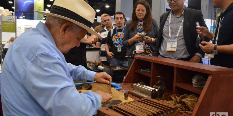 Un hombre prepara enrolla tabacos para los asistentes al Seatrade Global Event en el stand del puerto Tampa Bay. Foto: Marita Pérez Díaz.