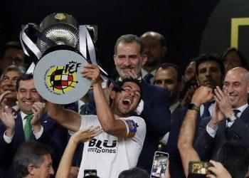 El capitán del Valencia CF, Daniel Parejo, levanta el trofeo, en presencia del rey Felipe y el presidente de la Junta de Andalucía, Juan Manuel Bonilla (i), tras vencer por 2-1 al FC Barcelona en la final de la Copa del Rey que ambos equipos han disputado esta noche en Estadio Benito Villamarín de Sevilla. EFE/Jose Manuel Vidal