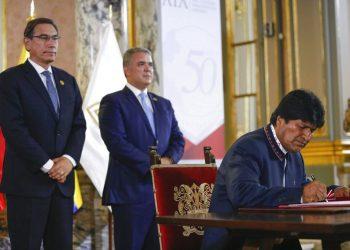 El presidente de Bolivia Evo Morales firma un documento ante la mirada de sus contrapartes Martín Vizcarra, de Perú, e Iván Duque, de Colombia, durante un encuentro de la Comunidad Andina en el 50mo aniversario del organismo, en el palacio de gobierno de Lima, Perú, el domingo 26 de mayo de 2019. Foto: Andre Valle/presidencia de Perú via AP.