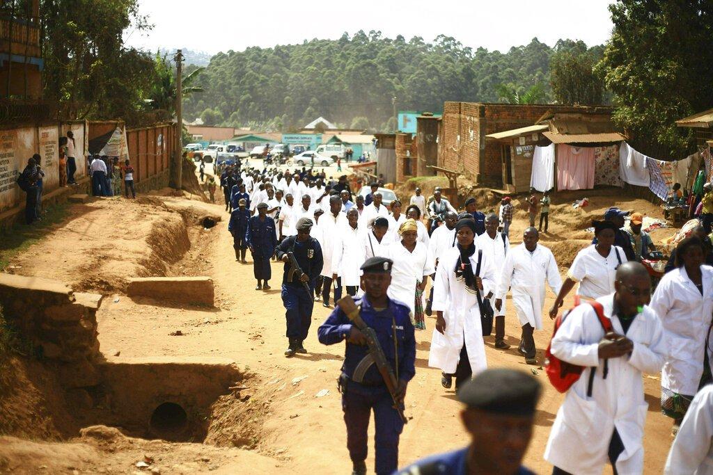 Médicos y trabajadores de salud marchan por la localidad de Butembo, en el este de la República Democrática del Congo, escoltados por fuerzas de seguridad después de que sujetos armados asesinaran a un epidemiólogo camerunés que trabajaba para la Organización Mundial de la Salud en el epicentro de una zona afectada por el ébola. (AP Foto/Al-hadji Kudra Maliro)