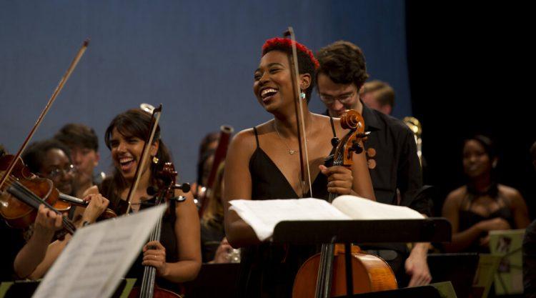 Integrantes de la Cuban American Youth Orchestra (CAYO) ríen durante una presentación en el Teatro Nacional de La Habana, el sábado 25 de mayo de 2019 en su primera gira por la isla. La orquesta juvenil cubano-estadounidense tiene músicos de importantes instituciones de ambos países como New World Symphony, Juilliard, el Instituto Superior de Arte de Cuba y la Orquesta de Cámara de Cuba. (Foto AP/Ismael Francisco)