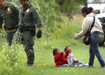 Una hondureña y sus dos hijos permanecen cerca de agentes de la Patrulla Fronteriza 10 de mayo de 2019 en el río Grande, cerca de Eagle Pass, en Texas, donde numerosas personas estaban cruzando a suelo estadounidense desde México en balsas. Foto: Bob Owen / The San Antonio Express-News vía AP.