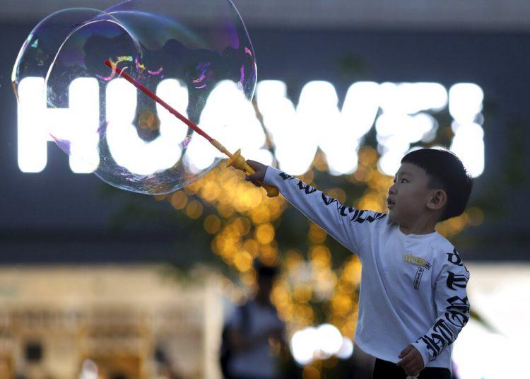 Un niño juega con pompas de jabón cerca del logo del gigante tecnológico chino Huawei, en Beijing, mayo de 2019. Foto: Ng Han Guan / AP.