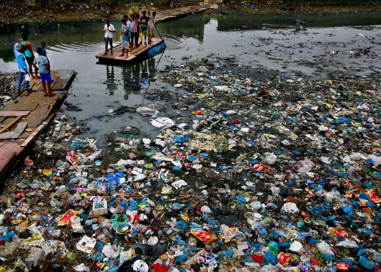 Un hombre conduce una balsa a través de un canal contaminado con bolsas de plástico y otros escombros en Mumbai, India, el 2 de octubre de 2016. Foto: Rafiq Maqbool / AP.