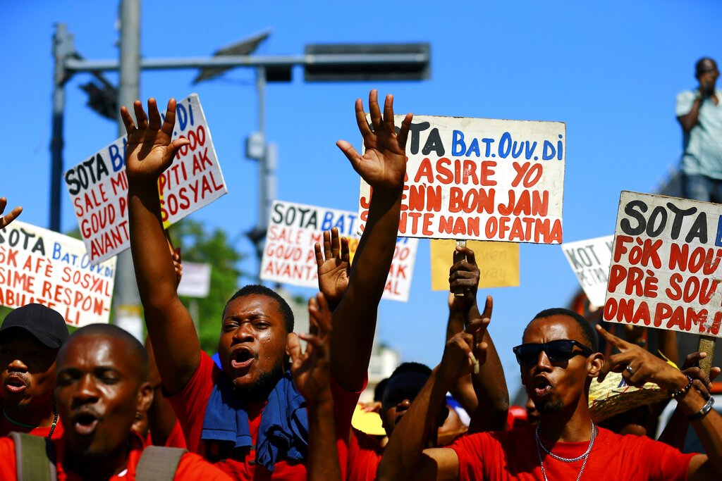 Manifestantes corean consignas contra el gobierno afuera del Buró Nacional de Seguros durante una manifestación del Primero de Mayo en Puerto Príncipe, Haití, el miércoles 1 de mayo de 2019. ( AP Foto/Dieu Nalio Chery)