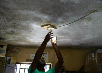 En esta imagen, tomada el 16 de abril de 2019, Johny Legagneur cambia una bombilla para un cliente en su tienda en Petion-Ville, Haití. Johny vive de cargar computadoras personales, celulares y bombillas recargables con un generador. (AP Foto/Dieu Nalio Chery)