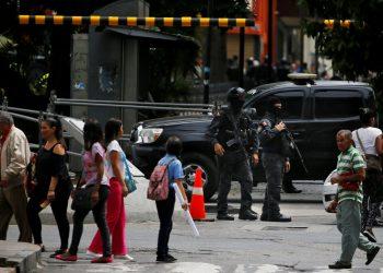 Agentes enmascarados del servicio de inteligencia de Venezuela montan guardia en la entrada del Congreso, controlado por la oposición, donde se ha bloqueado el acceso a los legisladores y al público, en Caracas, Venezuela, el martes 14 de mayo de 2019. (AP Foto / Fernando Llano)