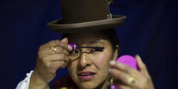 Una mujer aymara se maquilla mientras espera su turno para competir en el concurso Cholita Paceña 2019, en La Paz, Bolivia, el viernes 28 de junio de 2019. (AP Foto/Juan Karita)