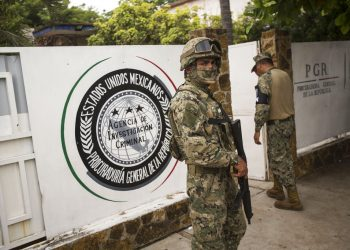 Un infante de Marina, al frente, y un miembro de la Guardia Nacional, atrás, vigilan afuera de una oficina de la Procuraduría General de la República adonde son enviados los migrantes antes de ser transferidos a Tapachula desde Arriaga, México, el domingo 23 de junio de 2019. Foto: Oliver de Ros / AP.