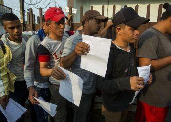 Migrantes centroamericanos hacen fila afuera de la Comisión Mexicana de Ayuda al Refugiado en Tapachula para obtener los documentos necesarios que les permiten permanecer en México, el jueves 20 de junio de 2019. Foto: Oliver de Ros / AP.