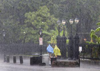 Dos personas caminan por la calle durante un aguacero en el French Quarter de Nueva Orleans, el domingo 14 de julio de 2019. Foto: David Grunfeld/The Advocate vía AP.