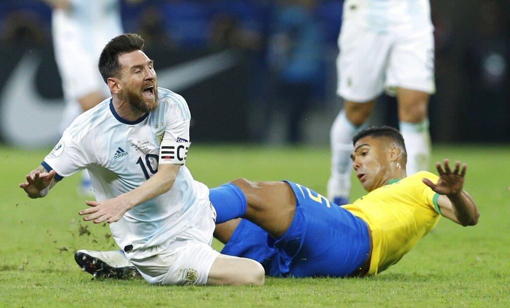 El delantero argentino Lionel Messi es derribado por el brasileño Casemiro en la semifinal de la Copa América, en Belo Horizonte, Brasil, el martes 2 de julio de 2019. Foto: Víctor R. Caivano / AP.