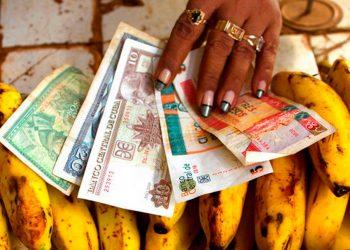 En esta foto de archivo una vendedora de alimentos distribuye pesos convertibles y pesos cubanos en su puesto en un mercado de verduras en La Habana, Cuba. Foto: AP/Ramón Espinosa.