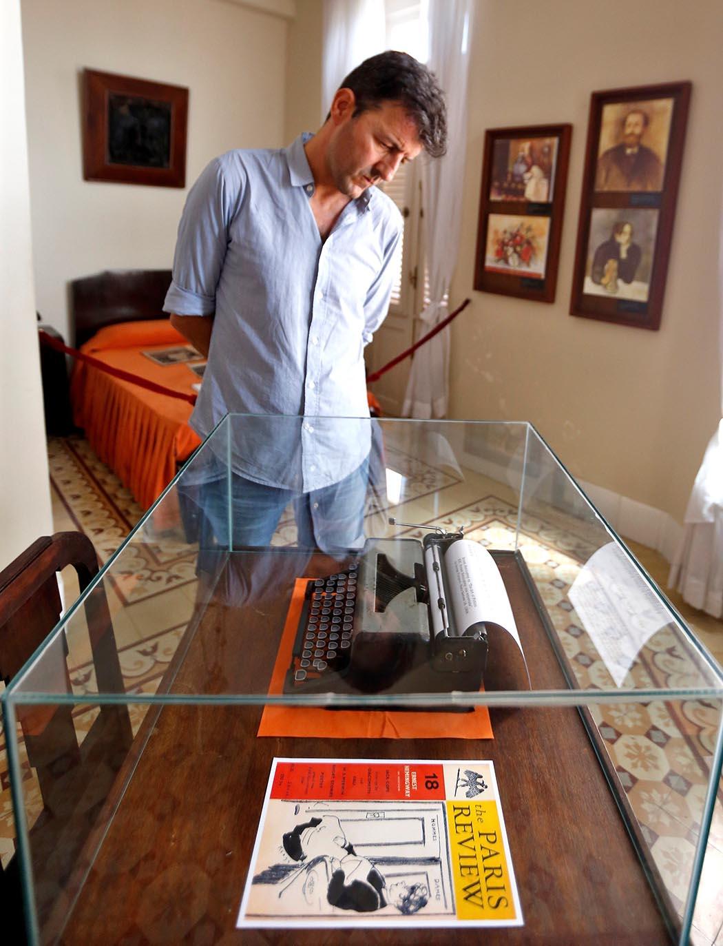 El periodista español Pablo López observa una máquina de escribir en la que fuera la habitación preferida de Ernest Hemingway en el Hotel Ambos Mundos, el 22 de junio de 2019, en La Habana. Foto:  Ernesto Mastrascusa / EFE.