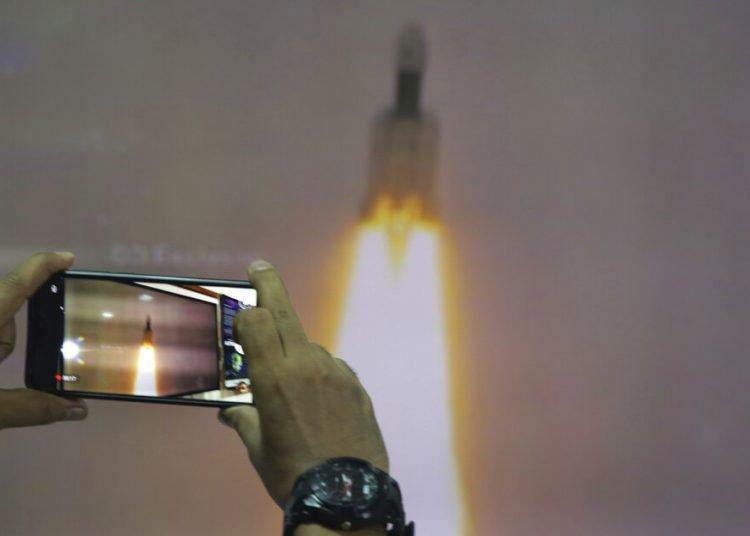 Un hombre en el Planetario Nehru de Nueva Delhi toma fotos de la transmisión por internet del despegue del vehículo de lanzamiento satelital Geosynchronous de la Organización de Investigación Espacial India en el centro espacial Satish Dhawan en la India. Foto: Manish Swarup / AP.