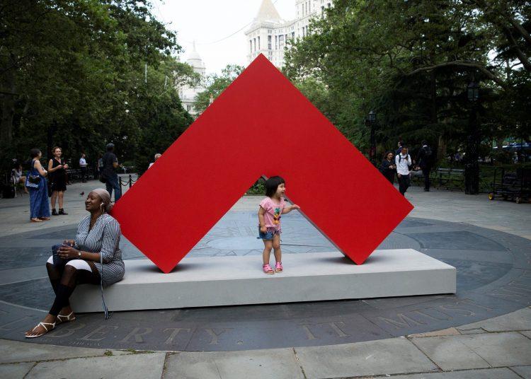Transeúntes interactúan con una obra de la primera gran exposición de esculturas exteriores de la artista cubana Carmen Herrera en Nueva York. Foto: Kena Betancur / EFE.