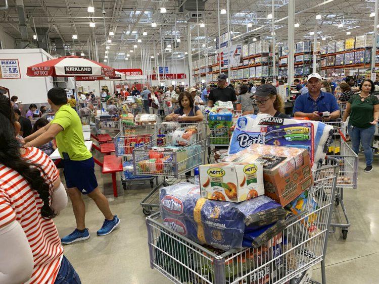 Compadores esperan en largas filas en un establecimiento de Costco, el 29 de agosto de 2019, en Davie, Florida, mientras hacen acopio de provisiones antes de la llegada del huracán Dorian. (AP Foto/Brynn Anderson)