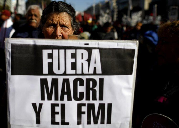 Una mujer sostiene un letrero que pide la salida del presidente Mauricio Macri y el Fondo Monetario Internacional mientras se realizan protestas contra políticas económicas y medidas de austeridad impuestas por el gobierno en Buenos Aires, Argentina, el jueves 22 de agosto de 2019. (AP Foto/Natacha Pisarenko)