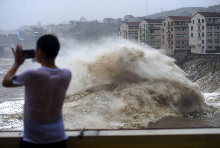 Un hombre graba con su celular el fuerte oleaje causado por la cercanía del tifón Lekima, en la ciudad de Wenling, en el la provincia oriental china de Zhejiang. (Han Chuanhao/Xinhua vía AP)