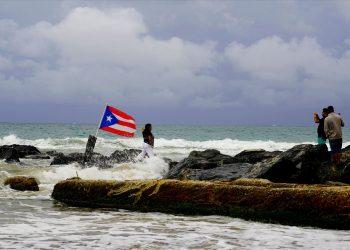 Una mujer posa para una fotografía con el mar y una bandera de Puerto Rico de fondo tras el paso de la tormenta tropical Dorian por la isla, en San Juan, Puerto Rico, el 28 de agosto de 2019. Foto: Ramón Espinosa/ AP.