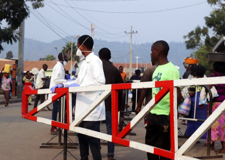 Personal médico revisa a personas en el lado congoleño del punto de revisión Poids Lourd en la frontera entre República Democrática del Congo y Ruanda, el jueves 1 de agosto de 2019. Foto: AP.