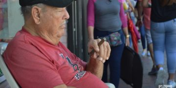 Un cubano fuma un tabaco y dormita frente a su negocio en la Calle Ocho. Foto: Marita Pérez Díaz.