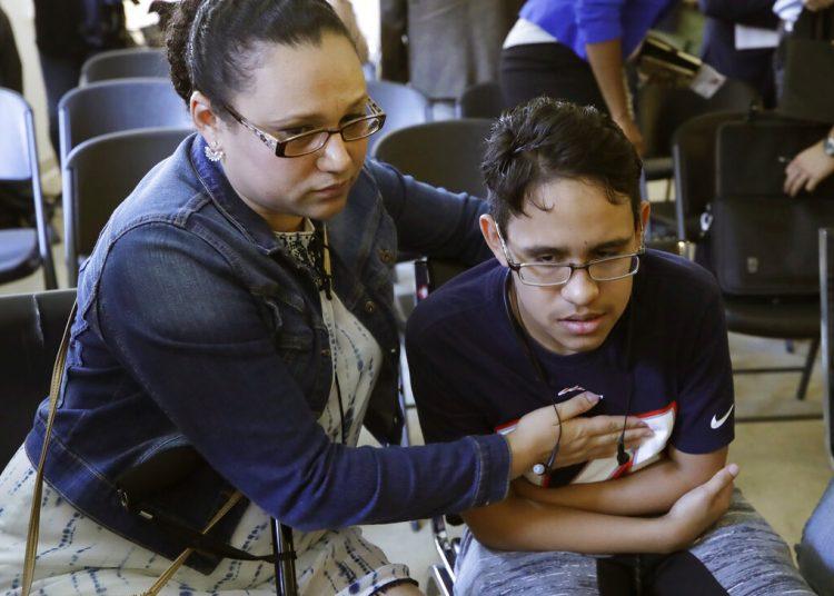La hondureña Mariela Sánchez consuela a su hijo Jonathan, de 16 años, quien sufre de fibrosis quística y viajó a Estados Unidos en busca de tratamiento médico que ahora podría interrumpirse por una nueva medida del gobierno de Donald Trump. Foto: Elise Amendola / AP.
