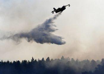 Un avión descarga agua sobre un incendio cerca de la localidad de Halkida, en la isla griega de Evia, el miércoles 14 de agosto de 2019. Foto: Michael Varaklas / AP.