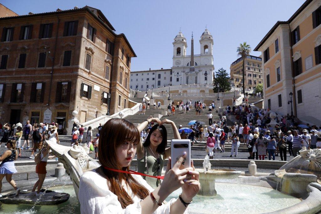 Turistas se toman fotos frente a la escalinata de la Plaza de España en Roma, el miércoles 7 de agosto de 2019. Foto: Gregorio Borgia / AP.