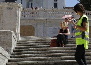 Policía pide a una mujer no sentarse en la escalinata de la Plaza de España en Roma, el miércoles 7 de agosto de 2019. Foto: Gregorio Borgia / AP.