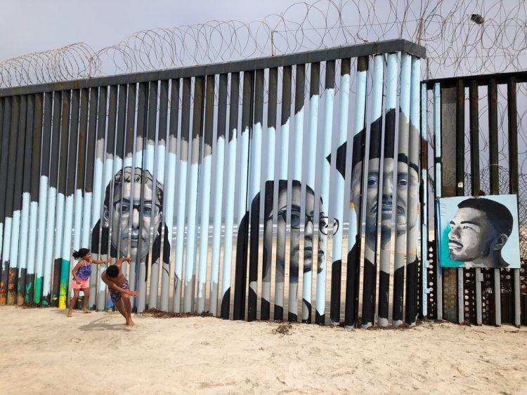 Dos niños juegan frente a un nuevo mural en el lado mexicano del muro fronterizo en Tijuana, México, el viernes 9 de agosto de 2019. Foto: Elliot Spagat/ AP.
