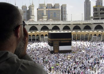 Un peregrino musulmán reza mientras observa como miles de fieles rodean la Kaaba, el edificio cúbico de la Gran Mezquita, antes del inicio de peregrinaje del Haj, en la ciudad santa musulmana de La Meca, Arabia Saudí, el 8 de agosto de 2019. (AP Foto/Amr Nabil)