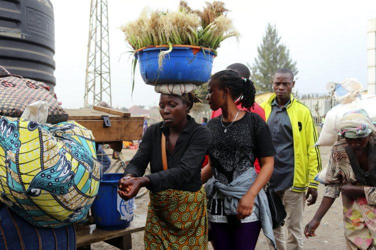 Varias personas se lavan las manos en la frontera entre la República Democrática del Congo y Ruanda, el jueves 1 de agosto de 2019. (AP Foto)