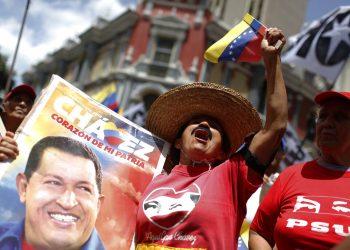 Una seguidora del gobierno que sostiene una imagen del fallecido presidente venezolano Hugo Chávez vitorea durante un mitin oficialista en Caracas, Venezuela, el sábado 27 de julio de 2019. Foto: Leonardo Fernández / AP / Archivo.