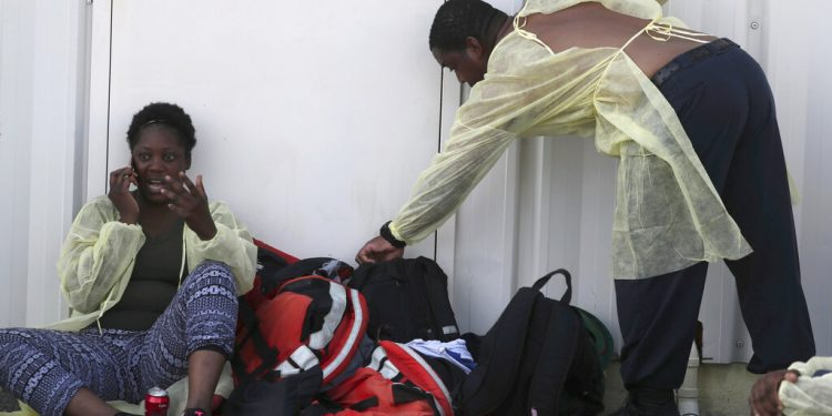 Una mujer (izquierda) habla por su celular tras ser evacuada de las islas Ábaco junto a otras personas luego del paso del huracán Dorian, en un aeropuerto privado en Nassau, Bahamas, el 5 de septiembre de 2019. (AP Foto/Fernando Llano)