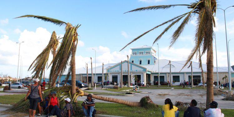 Varias personas esperan sentadas bajo unas palmeras destrozadas en el exterior del aeropuerto internacional Leonard M. Thompson tras el paso del huracán Dorian, en Marsh Harbour, en Islas Ábaco, Bahamas, el 5 de septiembre de 2019. (AP Foto/Gonzalo Gaudenzi)