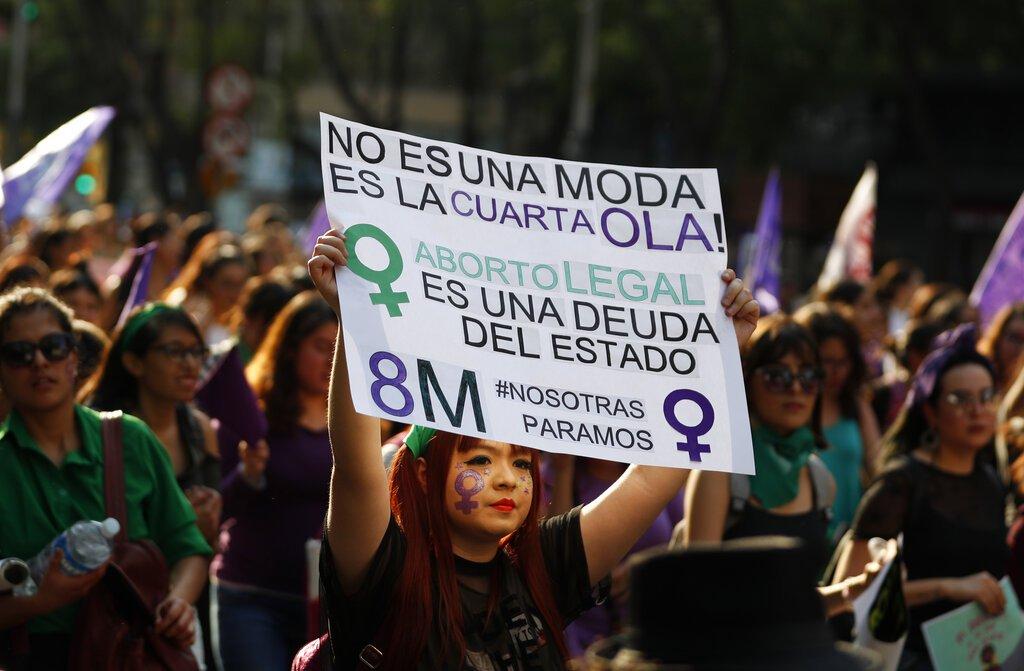 Una manifestante sostiene en lo alto un cartel de apoyo a la despenalización del aborto durante una movilización de feministas el Día Internacional de las Mujeres en la Ciudad de México. Foto: Rebecca Blackwell / AP / Archivo.