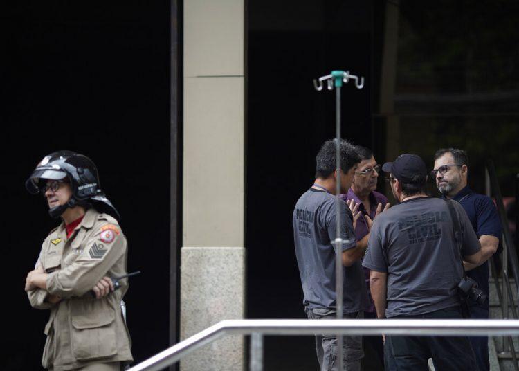 Un bombero e investigadores permanecen a la entrada del hospital Badim, donde un incendio dejó al menos 11 muertos, en Río de Janeiro, Brasil, el viernes 13 de septiembre de 2019. Foto: Leo Correa/AP.