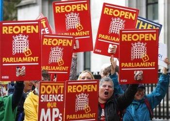 """Activistas contrarios al Brexit protestan delante del Supremo en Londres el martes 24 de septiembre de 2019, cuando se decidía sobre la legalidad de la suspensión parlamentaria. Los carteles dicen """"No silencien a nuestros parlamentarios"""" y """"Reabran el Parlamento"""".  (AP Foto/Frank Augstein)"""