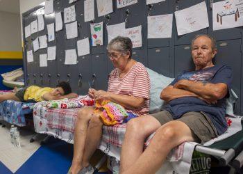 Personas sentadas en catres en el pasillo de la escuela secundaria North Myrtle Beach, que se está utilizando como refugio de evacuación de la Cruz Roja ante el huracán Dorian en Estados Unidos, el miércoles 4 de septiembre de 2019. Foto: Jason Lee/The Sun News via AP.