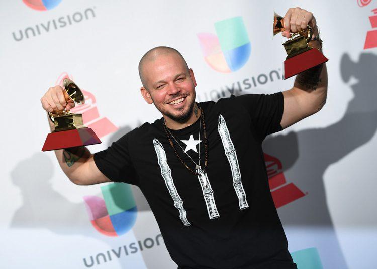 El puertorriqueño René Pérez, Residente, posa con dos premios Grammy Latinos ganados en 2017. Foto: umomag.com / Archivo.