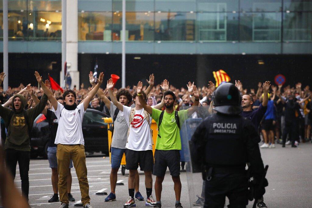 Policías antimotines vigilan las acciones de los manifestantes afuera del aeropuerto El Prat en Barcelona, España, el lunes 14 de octubre de 2019. Foto: Emilio Morenatti / AP.