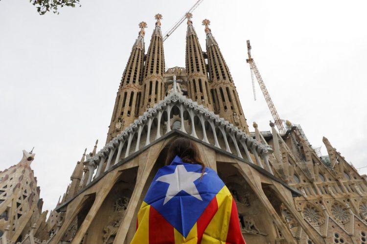 """Una manifestante envuelta en la """"estelada"""", la bandera independentista catalana, está frente a la basílica de la Sagrada Familia en Barcelona, España, viernes 18 de octubre de 2019. (AP Foto/Bernat Armangue)"""