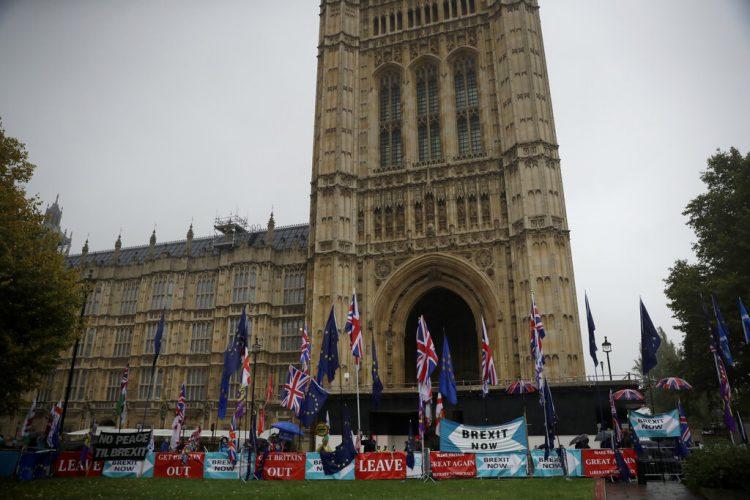 Contrarios al Brexit protestan con banderas europeas y británicas junto a pancartas colocadas por los partidarios de abandonar la Unión Europea, ante el parlamento británico, en Londres, el 24 de octubre de 2019. Foto: Matt Dunham/AP
