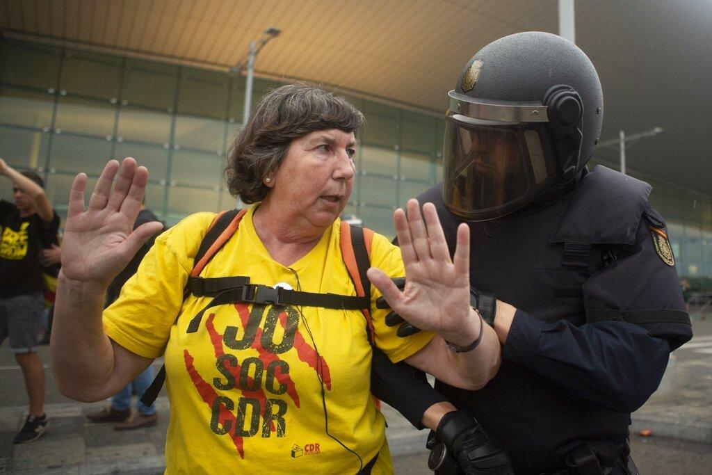 Un agente de la policía española habla con una manifestante proindependencia durante una manifestación en el aeropuerto de El Prat, en las afueras de Barcelona, España, el 14 de octubre de 2019. Foto: Joan Mateu / AP.