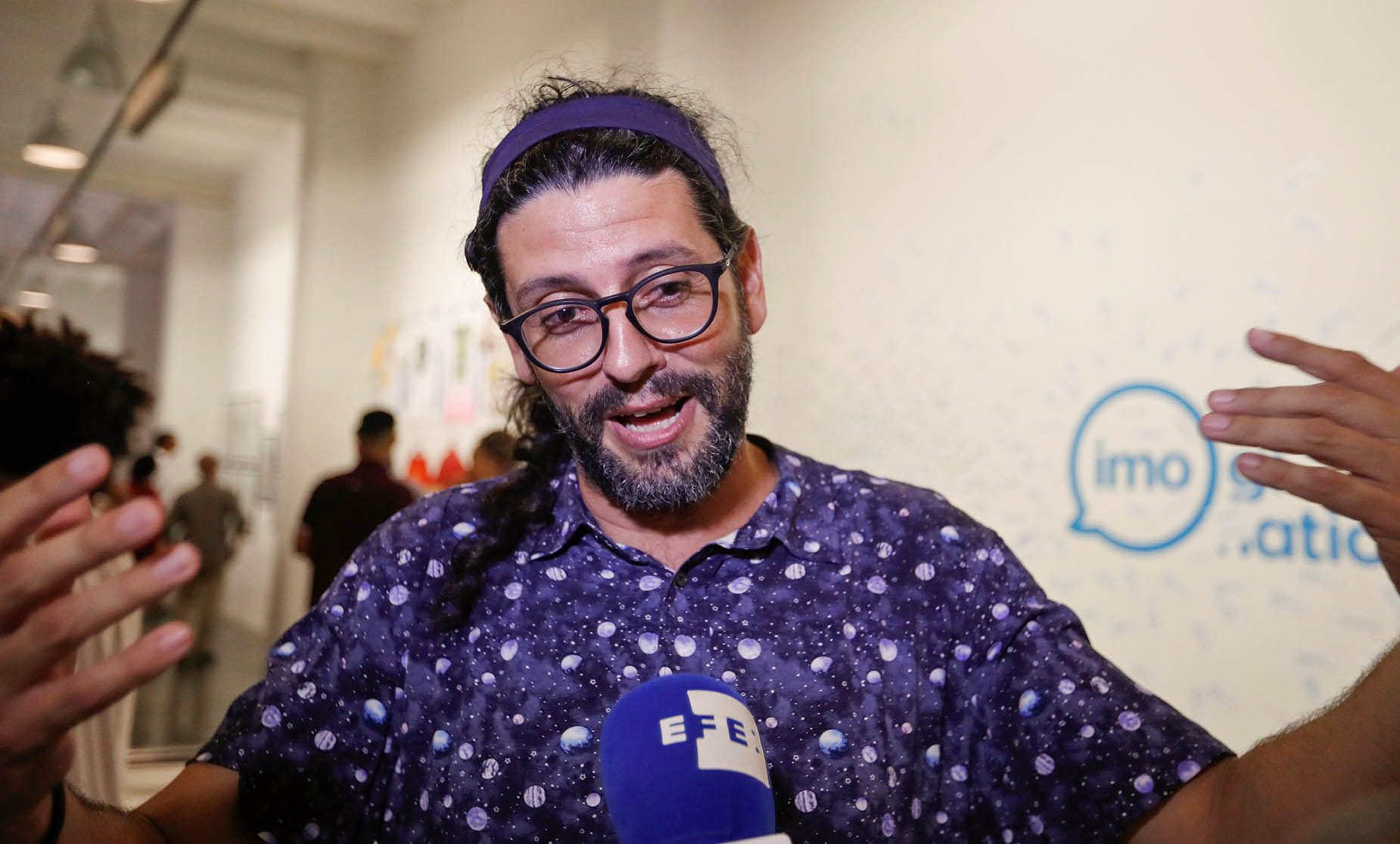 """El diseñador gráfico cubano Arnulfo Espinosa habla con Efe en la apertura de la exposición """"Conexiones"""", en la galería Factoría Habana. Foto: Yander Zamora / EFE."""