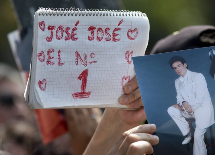 """Un admirador sostiene un cuaderno con el letrero """"José José el No.1"""" junto a una fotografía del fallecido cantante mexicano José José en un homenaje con karaoke en la Ciudad de México el viernes 4 de octubre de 2019. El llamado """"Príncipe de la canción"""" falleció el sábado 28 de septiembre en Miami a los 71 años. (Foto AP/Eduardo Verdugo)"""