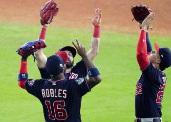 El dominicano Juan Soto (derecha) y su compatriota Víctor Robles festejan la victoria sobre los Astros de Houston en el primer juego de la Serie Mundial, el martes 22 de octubre de 2019 (AP Foto/Eric Gay)