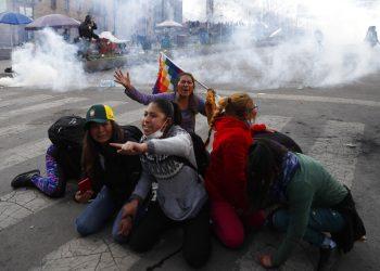 Manifestantes a favor del expresidente boliviano Evo Morales se protegen de las nubes de gas lacrimógeno lanzado por la policía, en La Paz, Bolivia, el 15 de noviembre de 2019. (AP Foto/Natacha Pisarenko)